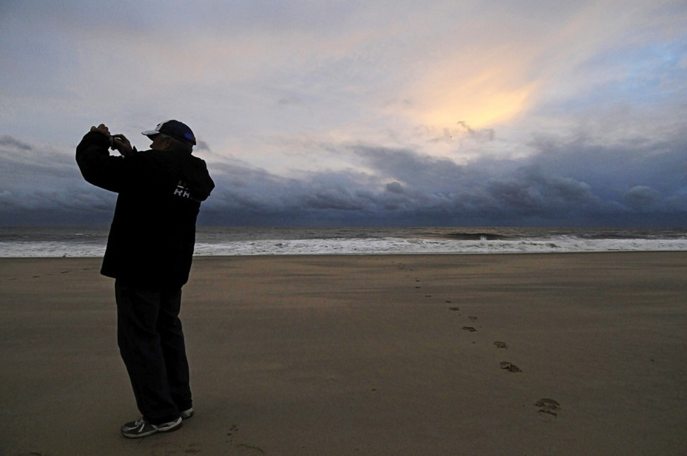 A man takes a picture of calm seas and sun-dappled clouds in the aftermath of Hurricane Sandy, at sunrise on Rehoboth Beach