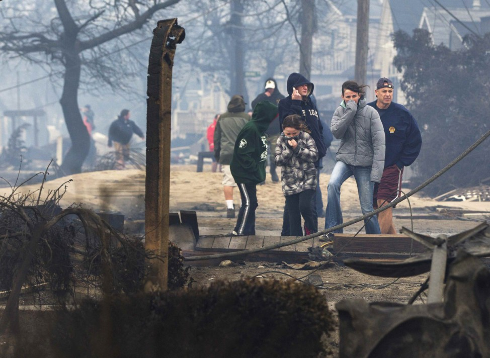 People stand among homes devastated by fire and Hurricane Sandy at the Breezy Point section of the Queens borough of New York