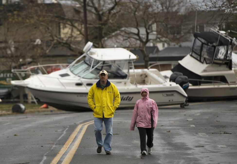 Residents walk along Broadway Avenue as they inspect damage from Hurricane Sandy in Point Pleasant Beach