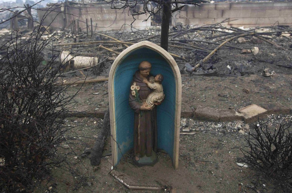 A statue is seen among homes devastated by fire and the affects of Hurricane Sandy in the Breezy Point section of the Queens borough of New York