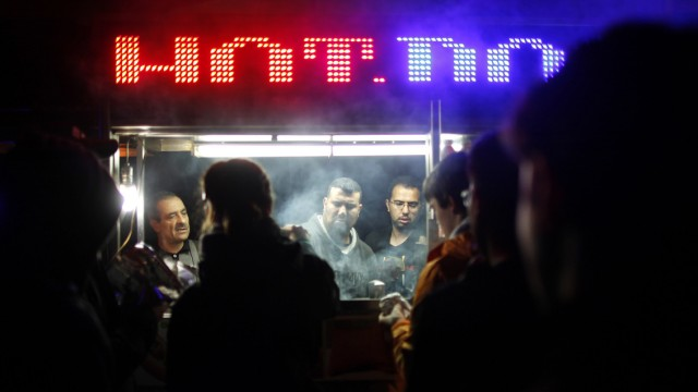 People line up to buy food from a cart in the aftermath of Hurricane Sandy in New York
