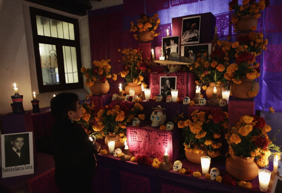 A visitor looks on at an art installation of skulls and images of artists at altars assembled with figures of cinema and culture of Mexico and Latin by artists for Day of the Dead celebrations in Mexico City