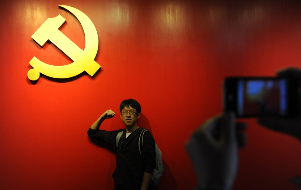 A university student takes his oath to join the Communist Party of China in front of an emblem for the CPC at the new South Lake Revolution Memorial Hall in Jiaxing