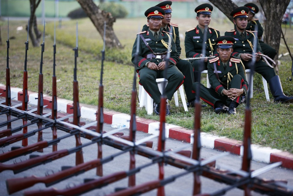 Laos honor guards and members of military orchestra sit behind guns as they prepare to welcome another foreign delegation arriving at Vientiane airport