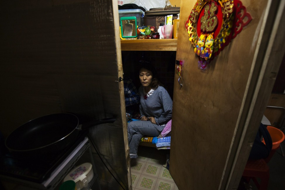 Li Rong, a 37-year-old woman, sits on a bed as she poses for photos in her 35 square feet (3.2 square metre) subdivided flat inside an industrial building in Hong Kong