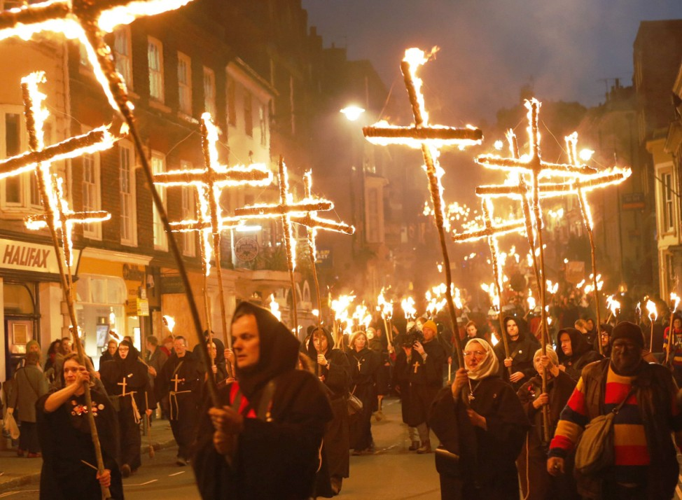 Participants in costume hold burning torches as they take part in one a series of processions during Bonfire night celebrations in Lewes