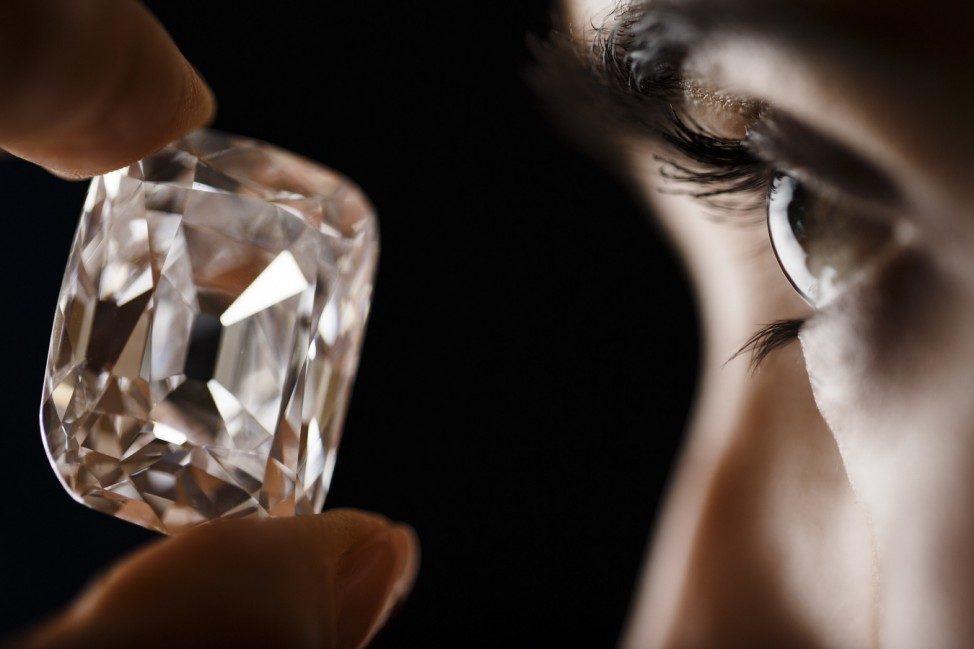 An employee poses with the Archduke Joseph diamond during an auction preview at Christie's in Geneva