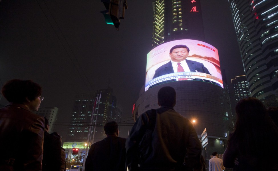 People watch a TV showing of a huge screen shows a news broadcast of China's Vice President Xi Jinping at the 18th Communist Party Congress at a crossroads in Shanghai