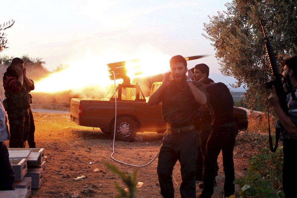 Free Syrian Army fighters fire a rocket towards a castle where pro-government forces are based, in Harem town, Idlib Governorate