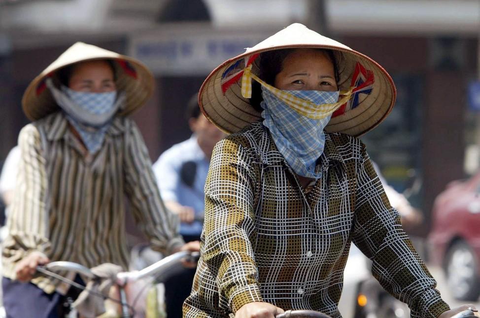 Radfahrerinnen in Hanoi schützen sich vor einer Ansteckung mit SARS, 2003