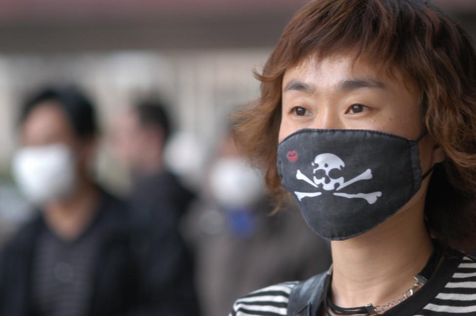 Frau in Peking schützt sich mit Mundschutz vor Ansteckung mit SARS, 2003
