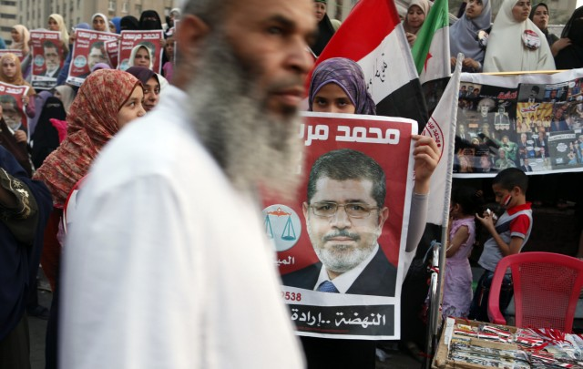 A supporter holds a poster of Egypt's President Mursi at Tahrir square in Cairo
