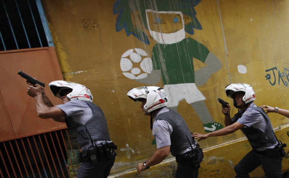 Police officers patrol in front of graffiti of a soccer player at the Brasilandia favela during a security operation in Sao Paulo