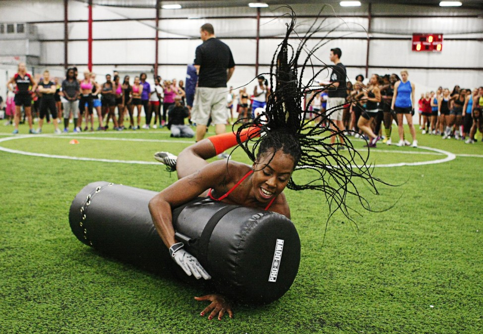 Sharp hits a tackle dummy at football tryouts for Atlanta Steam for the Lingerie Football League during drills in Fairburn