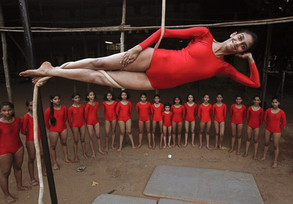 A girl practices a Mallakhamb pose while suspended from a rope at the Shree Samartha Vyayam Mandir in Mumbai