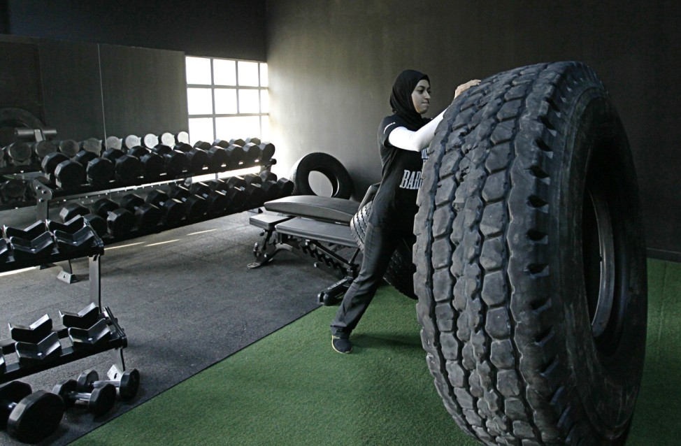 Emirati weightlifter Amna Al Haddad pushes a tyre during a training session in Dubai