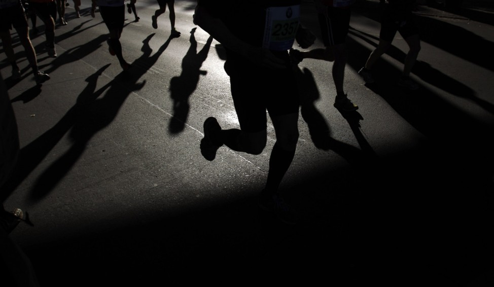 Athletes cast their shadows on the ground as they compete in the 39th Berlin Marathon in Berlin
