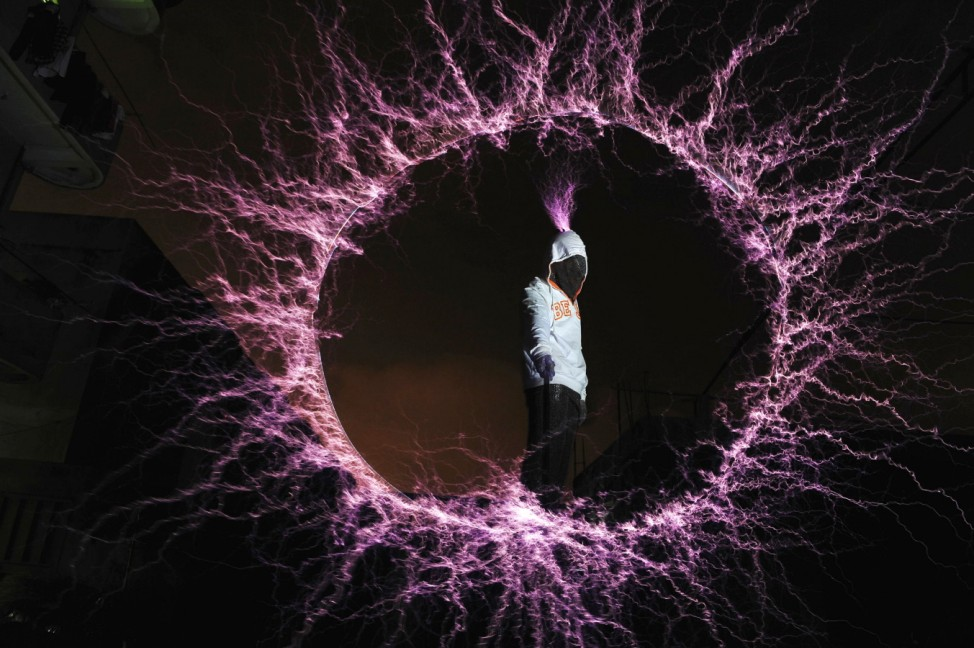 A Thunderbolt Craziness band member wears a metal suit as he forms a symbol from electric arcs using a metal stick while standing on tesla coils during a performance in Fuzhou