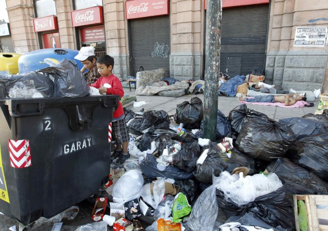 Children stand over a garbage container during a one-day nationwide strike in Buenos Aires
