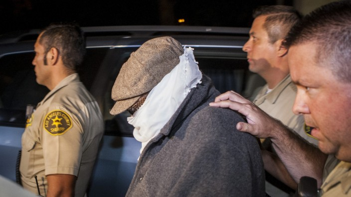 File photo of Nakoula Basseley Nakoula being escorted out of his home by Los Angeles County Sheriff's officers in Cerritos, California