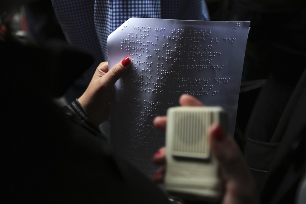 A visually impaired protester holds a sheet with braille as she takes part in an anti-austerity rally outside the Finance ministry in Athens