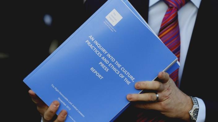 Regulierung der britischen Medien: Ein Mann trägt eine Kopie des Leveson Reports, als er das Queen Elizabeth II Conference Centre in London verlässt.