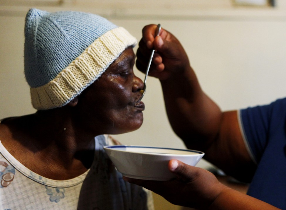 An AIDS patient is fed by a volunteer worker of the Sakhi-Sizwe AIDS care initiative in Orange Farm township, south of Johannesburg