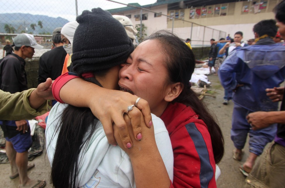 A woman cries after identifying a relative who was one of the flash flood victims after Typhoon Bopha hit New Bataan in Compostela province
