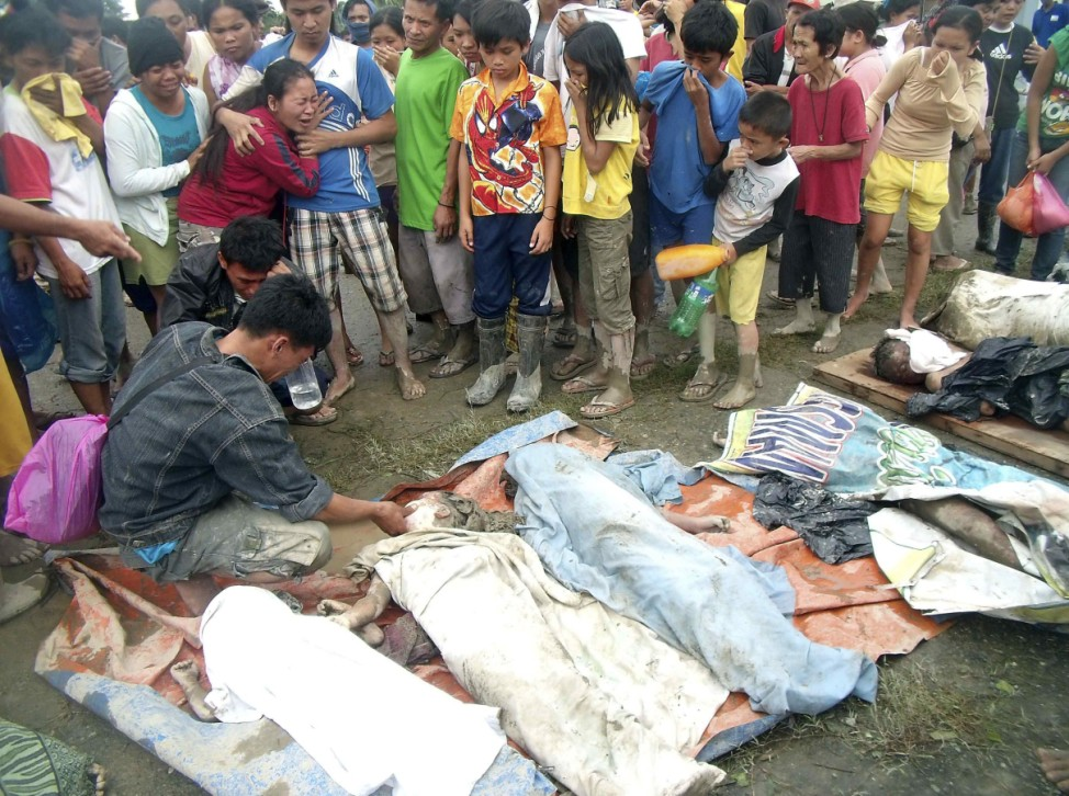A family cries after finding their relative among victims of a flash flood after Typhoon Bopha hit New Bataan, Compostela province