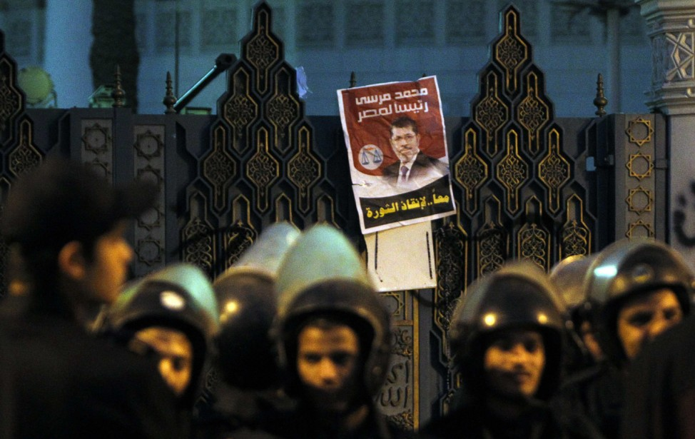 Riot police stand guard in front of  the presidential palace in Cairo