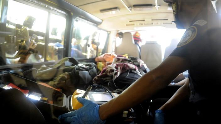 US-Software-Pionier auf der Flucht: Unter Blitzlichtgewitter wird John McAfee in ein Polizeikrankenhaus in Guatelama gebracht.
