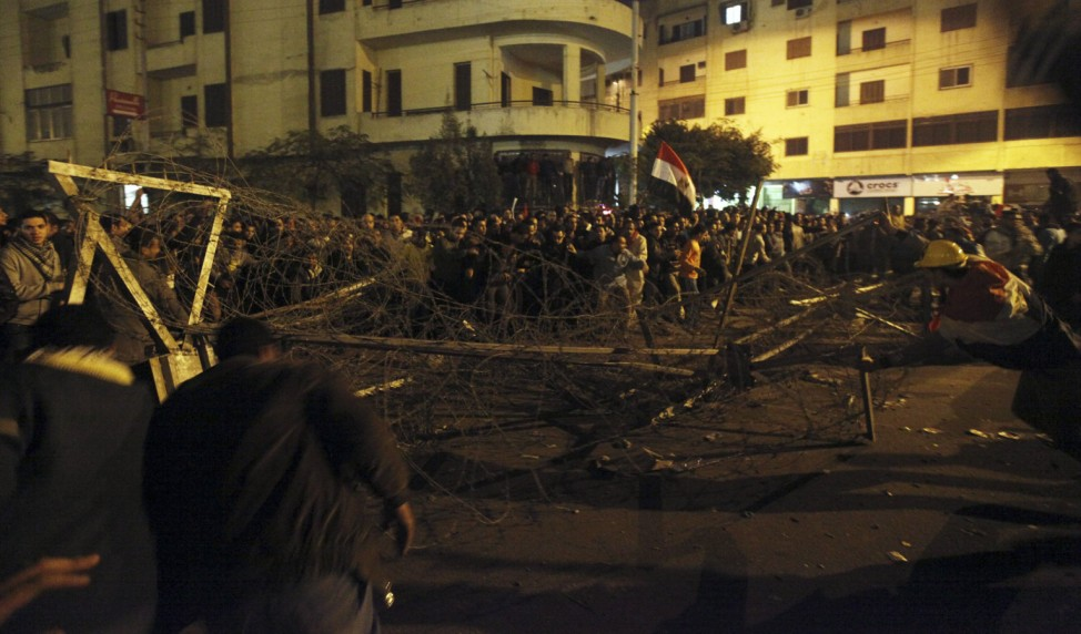 Anti-Mursi protesters remove barbed wire barricades blocking a road leading to the presidential palace in Cairo