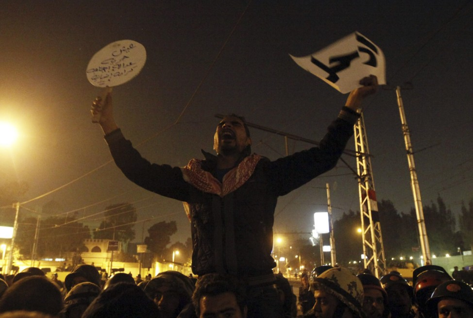 An Anti-Mursi protester shouts slogans in front of members of the Republican Guard blocking a road leading to the presidential palace in Cairo