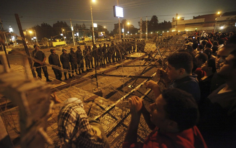 Members of the Republican Guard block a road leading to the presidential palace as anti-Mursi protesters gather in Cairo