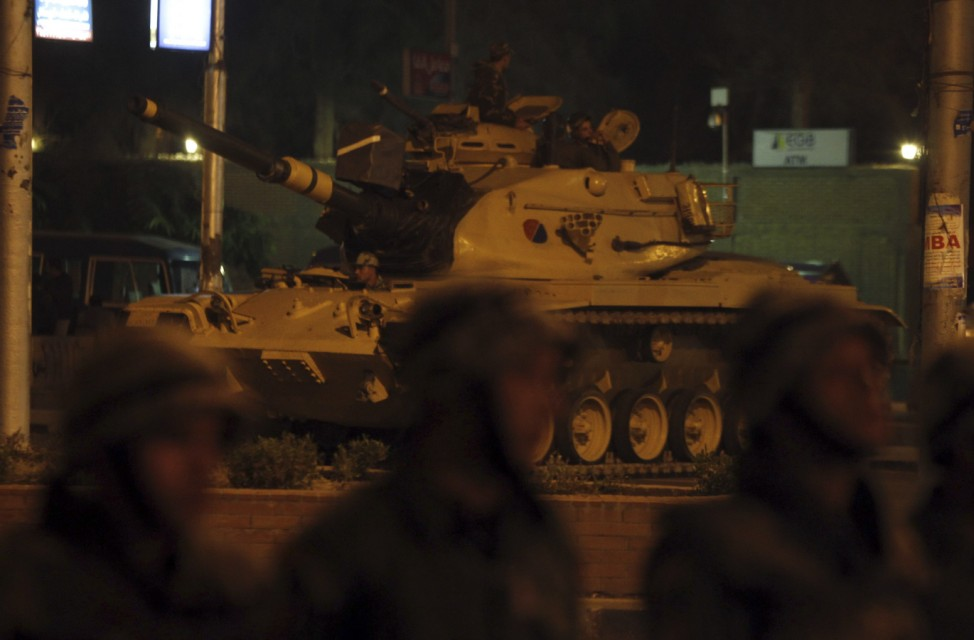 A military tank with members of the Republican Guard are seen on a road leading to the presidential palace during an anti-Mursi protest in Cairo