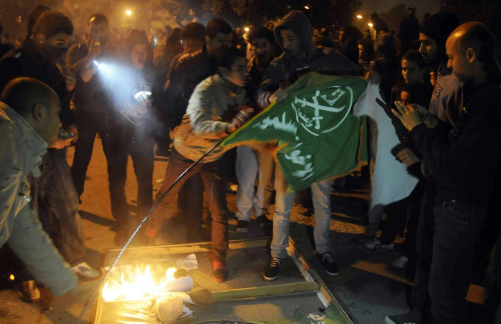 Anti-Mursi protesters set fire to a Muslim Brotherhood flag outside its main office in Cairo