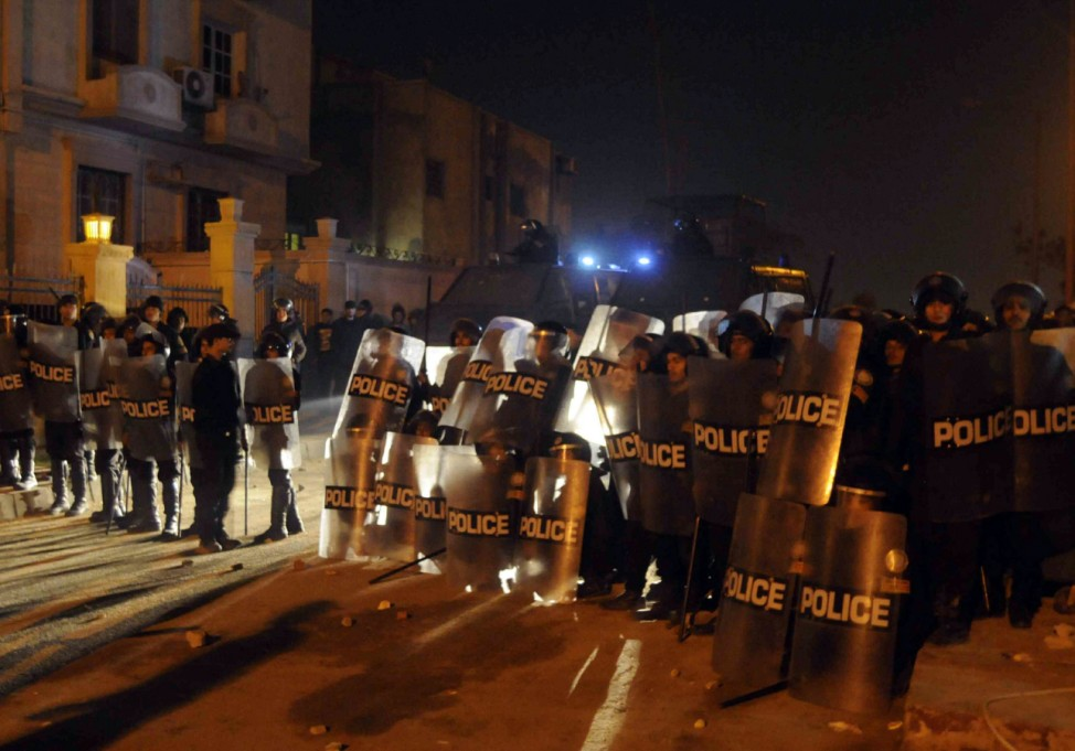 Riot police form a line as protesters against Egypt's President Mursi stormed and started a fire at the Muslim Brotherhood's headquarters in Cairo