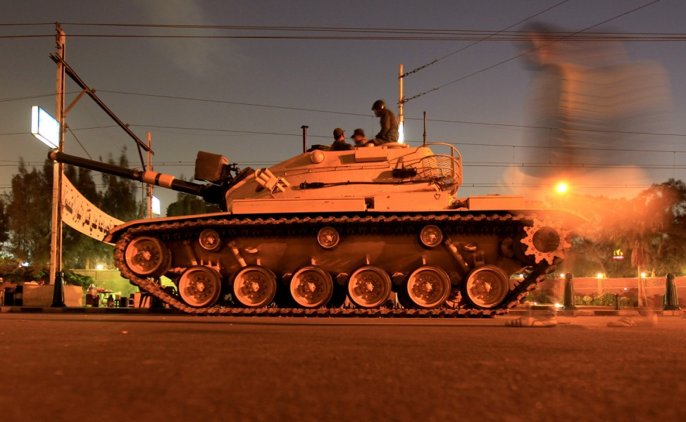 A man walks past an army tank from the republican guard in front of the presidential palace in Cairo