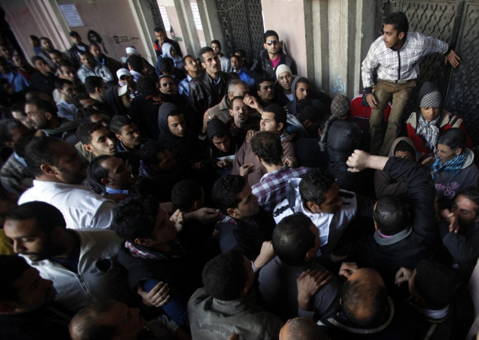 People clash with anti-Mursi protesters, after the protesters blocked the gate of a government building near Tahrir Square in Cairo