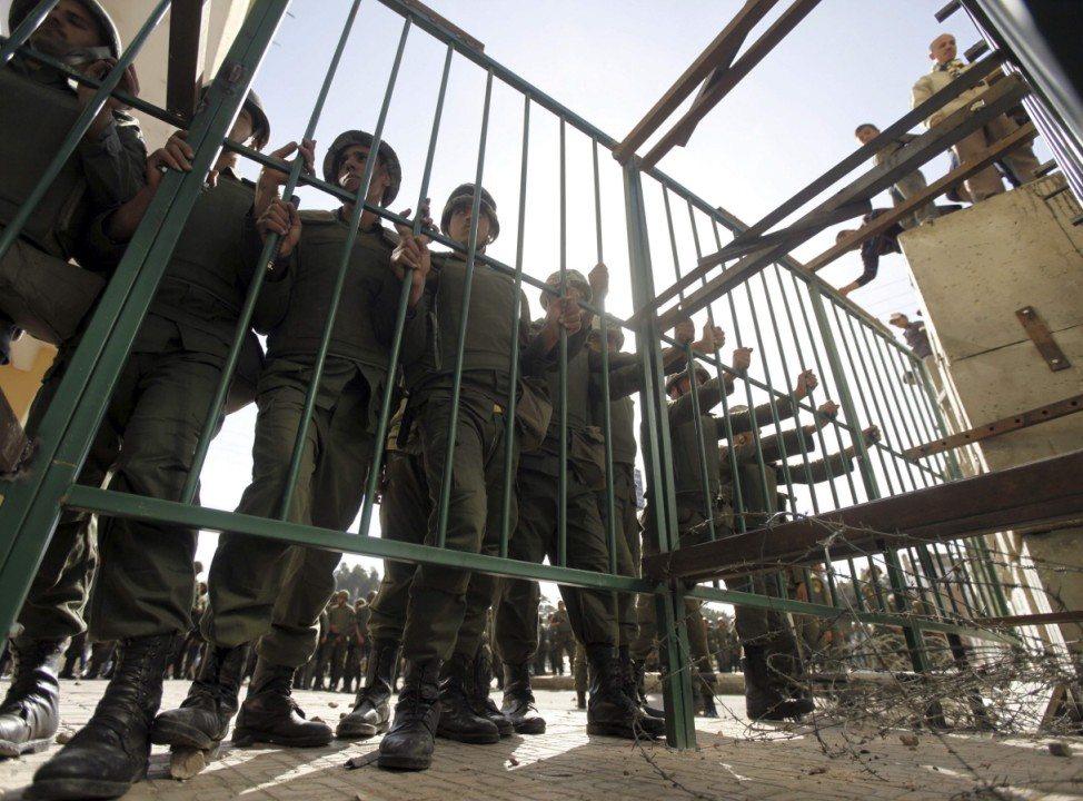 Members of the Republican Guard stand behind a gate to block a road that anti-Mursi protesters are trying to use to reach the presidential palace in Cairo