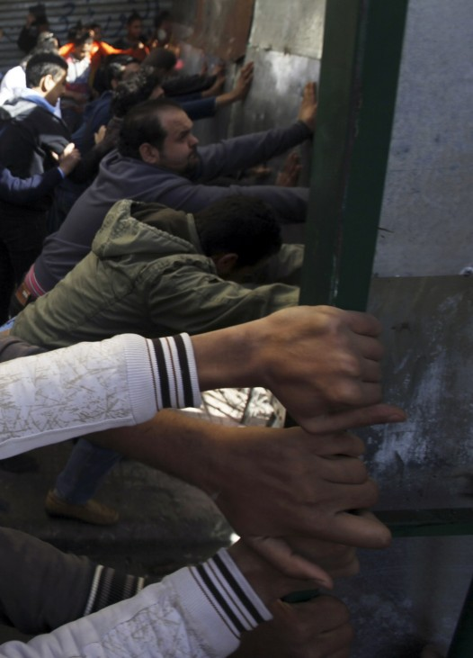 Anti-Mursi protesters attempt to open a gate leading to a road in front of the presidential palace in Cairo