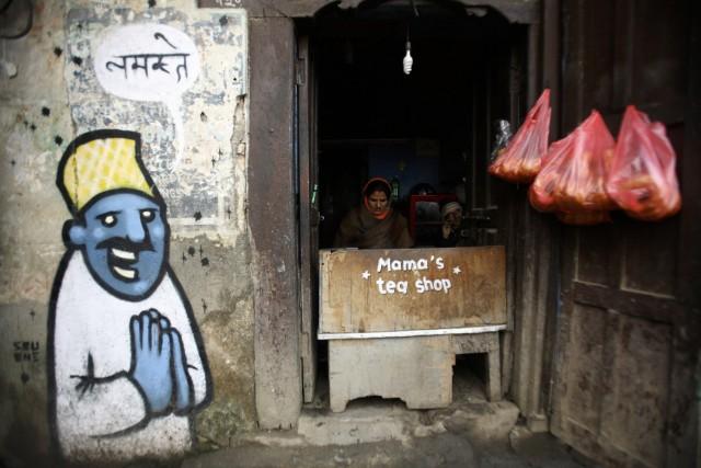 A woman is seen as she prepares tea at her tea shop in Kathmandu