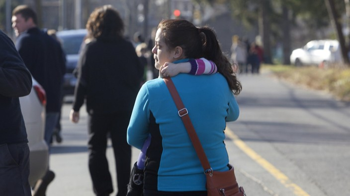 A woman carries her daughter following a shooting at Sandy Hook Elementary School in Newtown