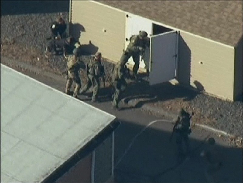 Police search a building after a shooting at Sandy Hook Elementary School in Newtown