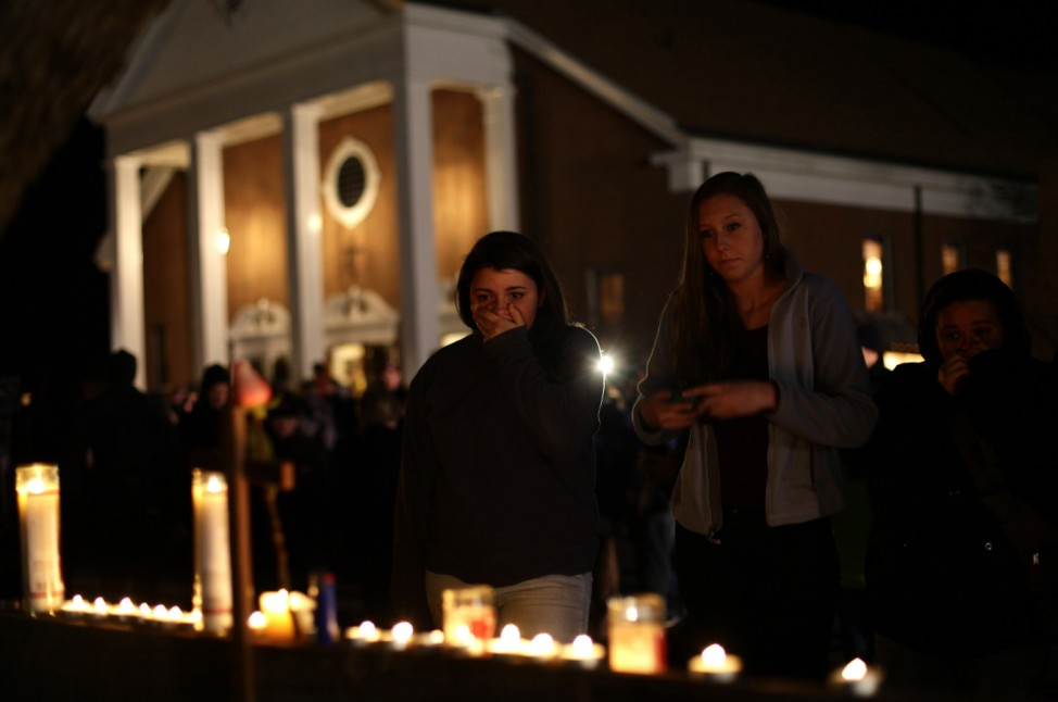 A woman covers her mouth as others look on stand near candles outside Saint Rose of Lima Roman Catholic Church near Sandy Hook Elementary School, where a gunman opened fire on school children and staff in Newtown,