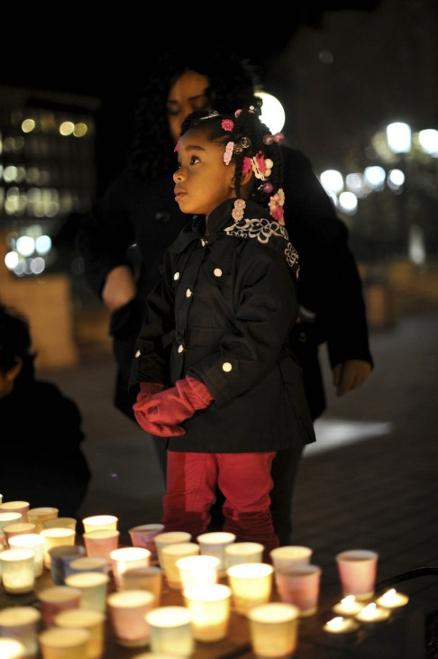 Aminah Crawford joins in a vigil commemorating victims of a Connecticut elementary school shooting in Oakland
