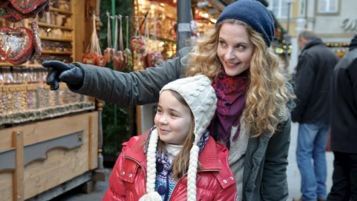 """Miriam (Diana Amft, hinten) versucht im Film """"Obendrüber, da schneit es"""", ihrer Tochter Julchen (Lara Sophie Rottmann, vorne) das erste Weihnachten ohne Papa so schön wie möglich zu machen."""