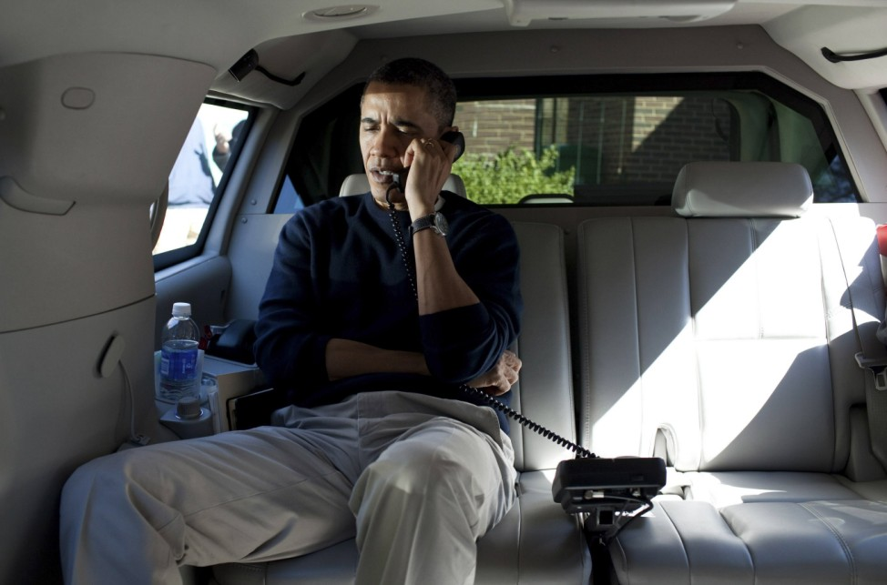 U.S. President Obama talks on a phone with Afghanistan's President Hamid Karzai from inside his vehicle outside Washington