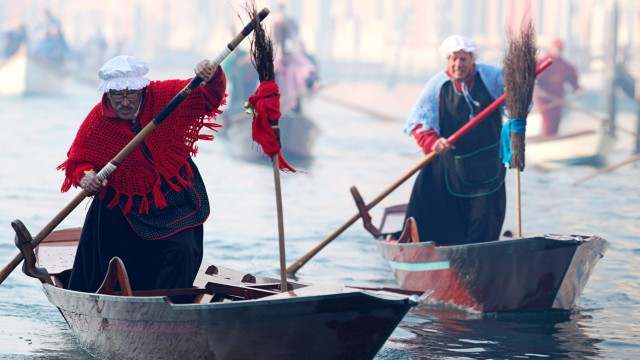 Men in traditional 'Befana' costumes compete in the 'Regatta of Befane' on the Grand Canal in Venice