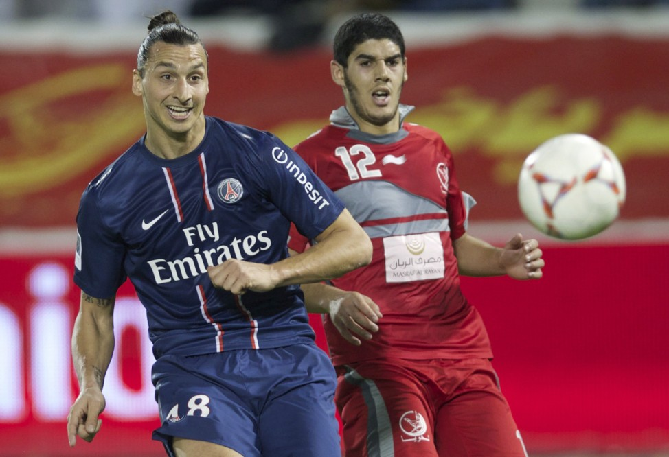 Paris Saint-Germain's Zlatan Ibrahimovic of Sweden fights for the ball with Lekhwiya's Karim Boudiaf during their friendly soccer match in Doha